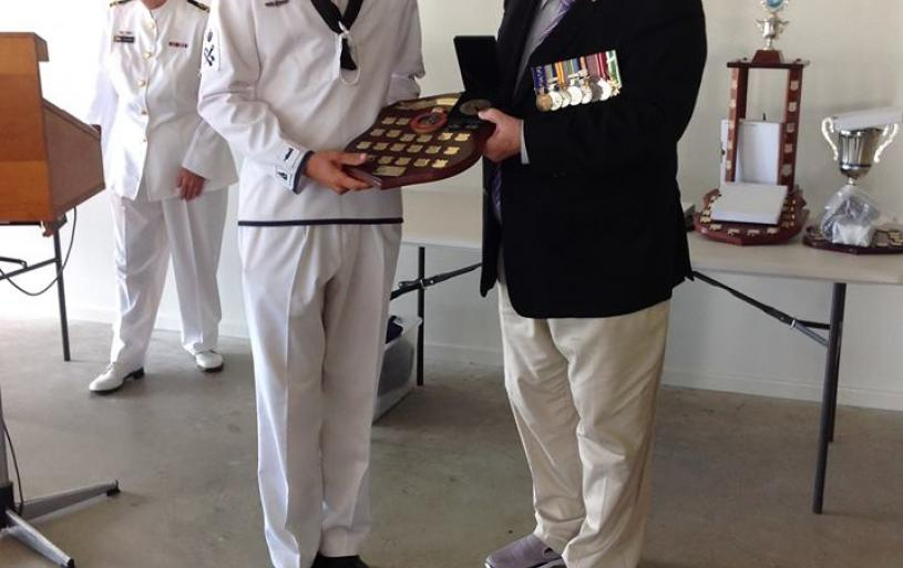 CDR Nield presents a prize to a Training Ship Paluma Australian Naval Cadet.